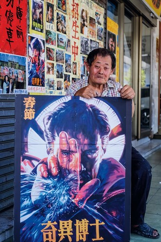 Yan Jhen-fa proudly poses with his hand-painted billboard for the film Doctor Strange (2016).