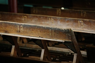 The old cypress seats of the Ruiwudan Theater are still there today. The row and seat numbers are carved right into the wood, as are the marks of the passage of time.