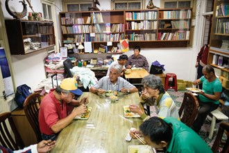 At the end of a day's work, Fr. Moal eats with the people he has taken in, using the opportunity to offer encouragement.
