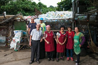 Fr. Moal (front row, left) uses recycling to help people who have been injured in some way regain their confidence and their joy in life. (photo by Chuang Kung-ju)