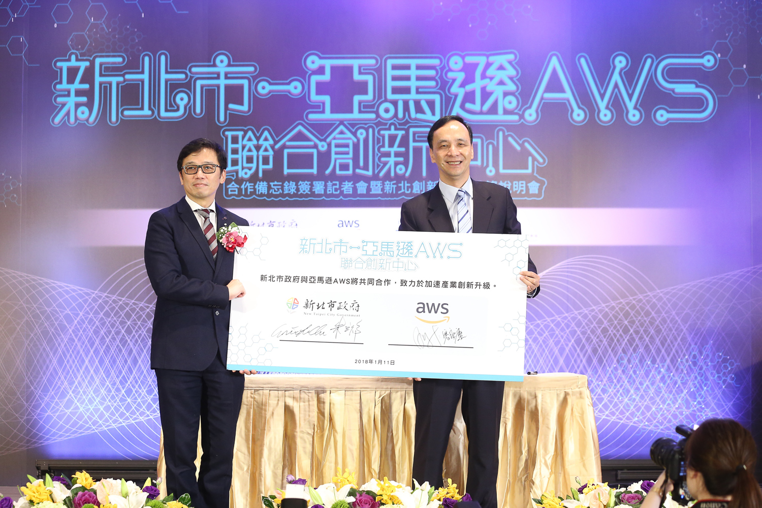 New Taipei Mayor Eric Chu (right) and Alex Yung, corporate vice president of Amazon Web Services, hold up a placard showing a signed agreement between the city government and AWS on jointly establishing an internet innovation center Jan. 11 in the northern Taiwan metropolis. (Courtesy of NTCG)