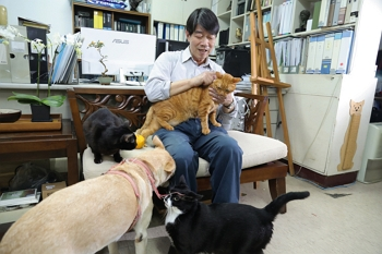 Ko Hung-tu is full of compassion, and has a great relationship with the stray dogs and cats to whom he has given refuge. (photo by Jimmy Lin)