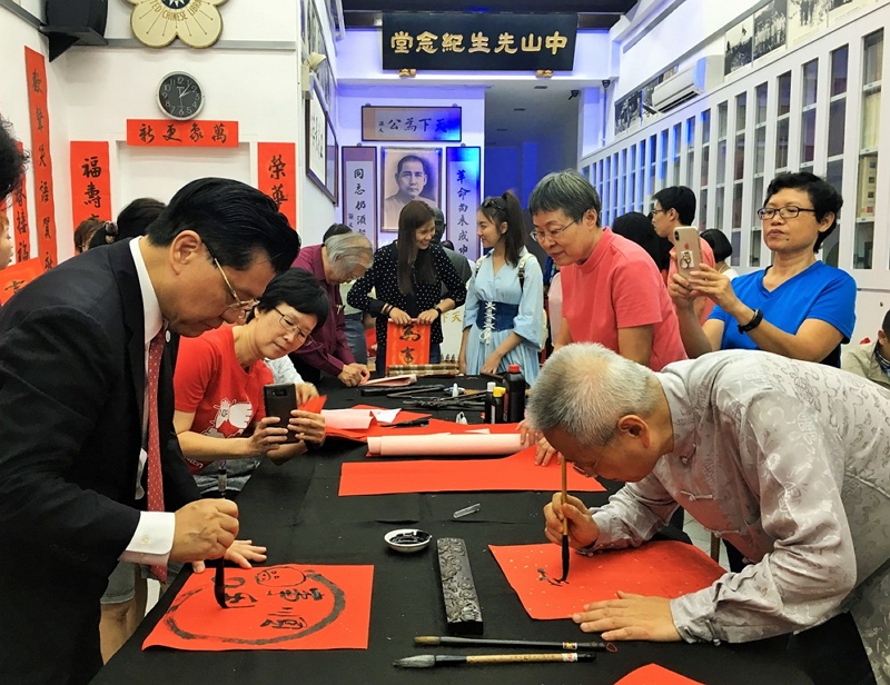 Representative Francis Liang (left) and Mr. Heman Chen, Senior advisor of the Overseas Community Affairs Council, writing auspicious Chinese New Year messages at the request of those present at the event.
