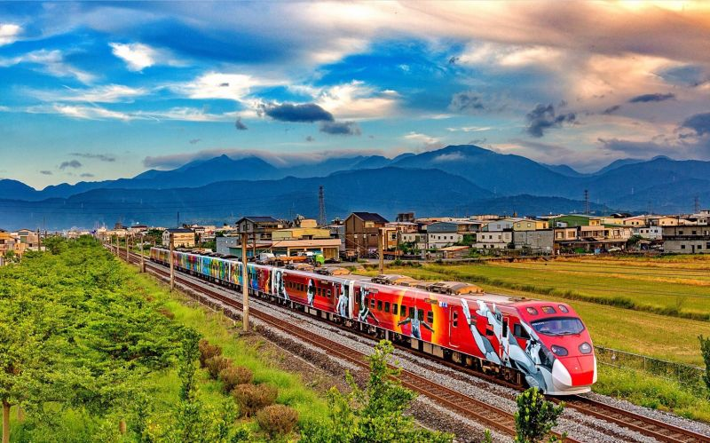 A Taiwan Railways Administration Puyuma express train sporting livery based on the paintings of Amis artist Yosifu rolls through the scenic landscape of eastern Taiwan. (Courtesy of Yiyuan Resort)