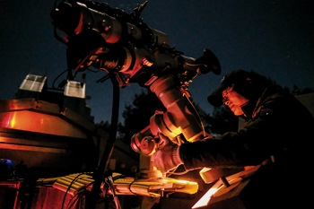 Lin Hung-chin operates his telescope with practiced skill. This device, which he has been toting into the mountains for over 30 years, has kept him company on countless cold nights.