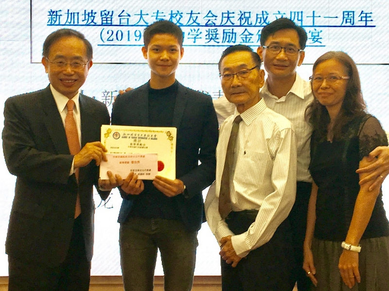 Director Jerry K. H. Chen (first from left) presents a special award to the top scorer of the high school category as the latter's family members looked on