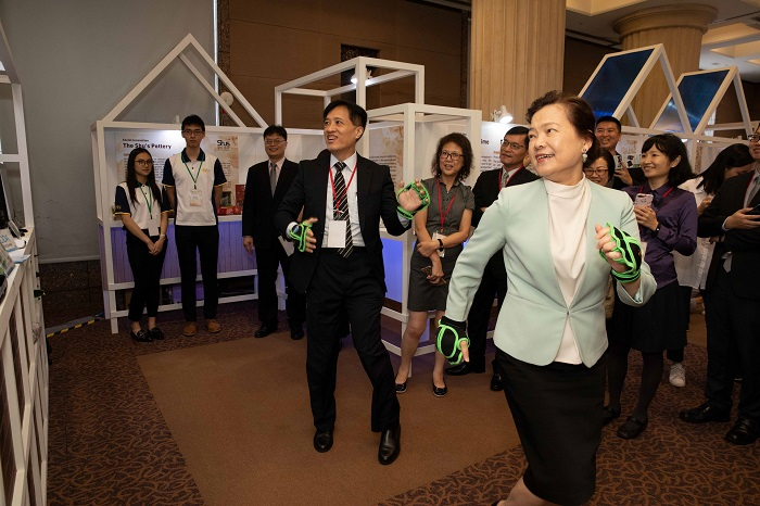MOEA Deputy Minister Wang Mei-hua (front, right) tries an innovative product displayed at the SMEA-hosted APEC Local Innovation Ecosystem Forum June 24 in Taipei City. (Courtesy of MOEA)