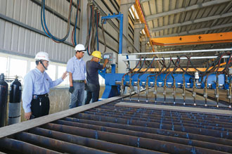 Hsu Fa-hsih, left, senior manager of Myanmar Century Steel Structure, inspects a production line at the company's plant in Thilawa Special Economic Zone in Yangon. (Photo by Chen Mei-ling)