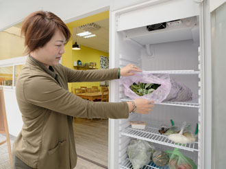 A volunteer examines donated food items at a public refrigerator set up by Alliance of Taiwan Foodbanks in Taichung.(Photo by Chin Hung-hao)