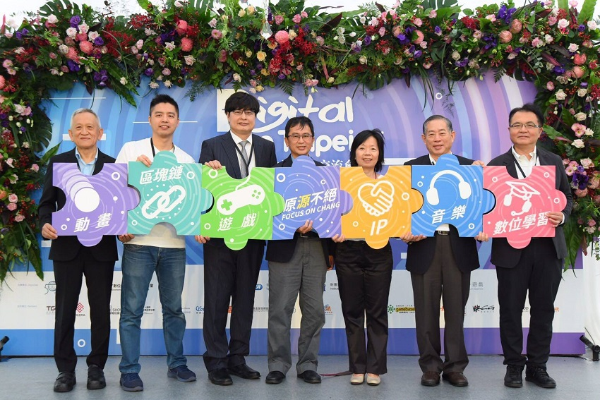 Business representatives and officials hold up placards promoting Digital Taipei at the event's opening ceremony July 12 at Taipei Expo Park. (Courtesy of IDB)
