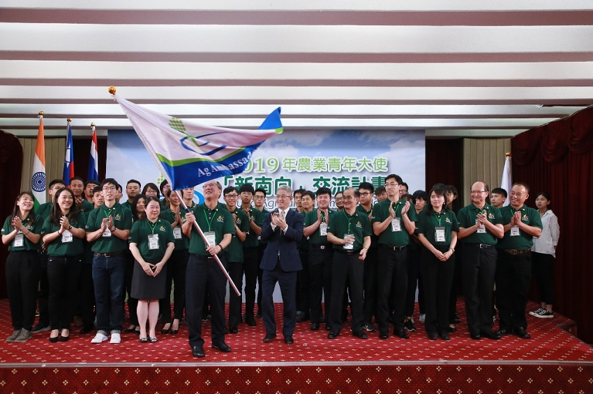 Deputy MOFA Minister Hsu Szu-chien (center) applauds as an administrator waves the Taiwan Young Agricultural Ambassadors NSP Exchange Program flag Aug. 2 in Taipei City. (MOFA)