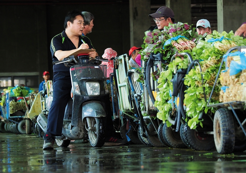 A buyer rides a small scooter among vegetable sellers as he places orders.