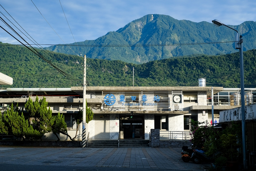 Fengtian Train Station in the early morning: The sun is rising on a tranquil scene, ringed by mountains.