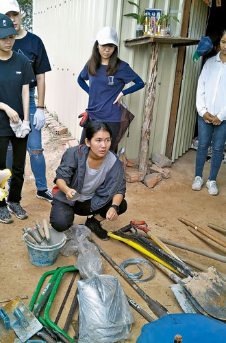 Bun Chou, center, a group leader and translator for Taiwan-headquartered social enterprise ELIV Co., explains the implements that will be used to build an outdoor toilet during a volunteer mission to Siem Reap province this summer. (Photo by Oscar Chung)