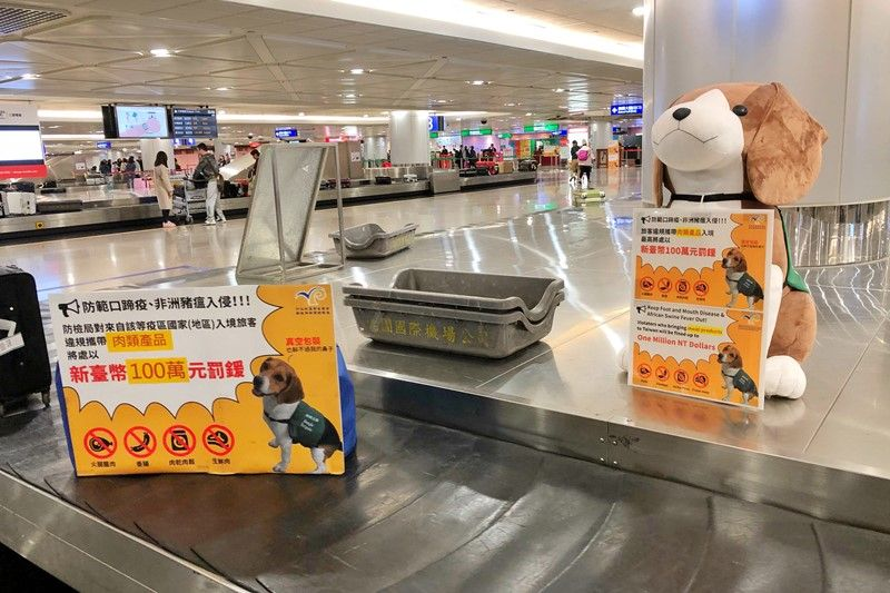 Signs at Taiwan Taoyuan International Airport warn passengers of the NT$1 million maximum fine for illegally bringing meat products into the country. (CNA)