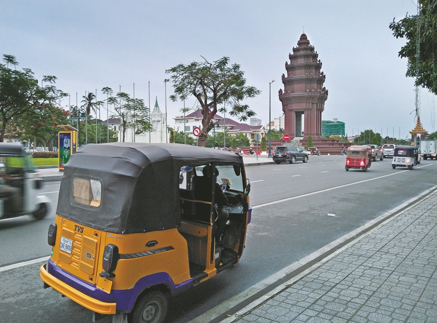 Vehicles drive past the Independence Monument in Phnom Penh, built to mark Cambodia's independence from France in 1953. (Photo by Oscar Chung)
