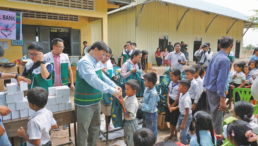 FCB workers hand out donations at a primary school in eastern Cambodia in June. (Photo courtesy of First Commercial Bank)