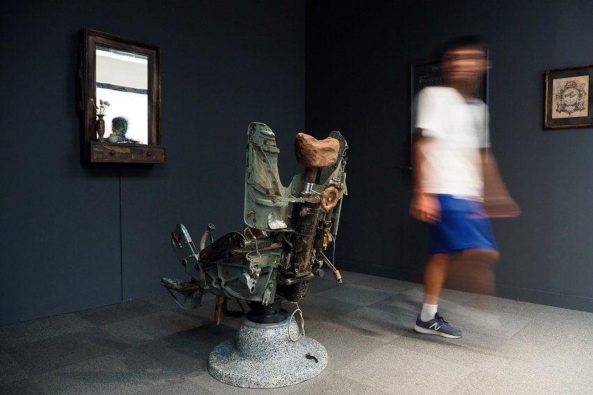 Bang Nhat Linh's The Vacant Chair (2013–2015) depicts conflict and tolerance in the aftermath of the Vietnam War. In the work, a video of a South Vietnamese barber shaving a former North Vietnamese soldier plays in front of the pilot's seat from a fighter plane recast as a barber's chair. (photo by Jimmy Lin)