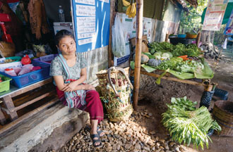 A Mae La camp resident sells vegetables in a market. (Photo by Chin Hung-hao)