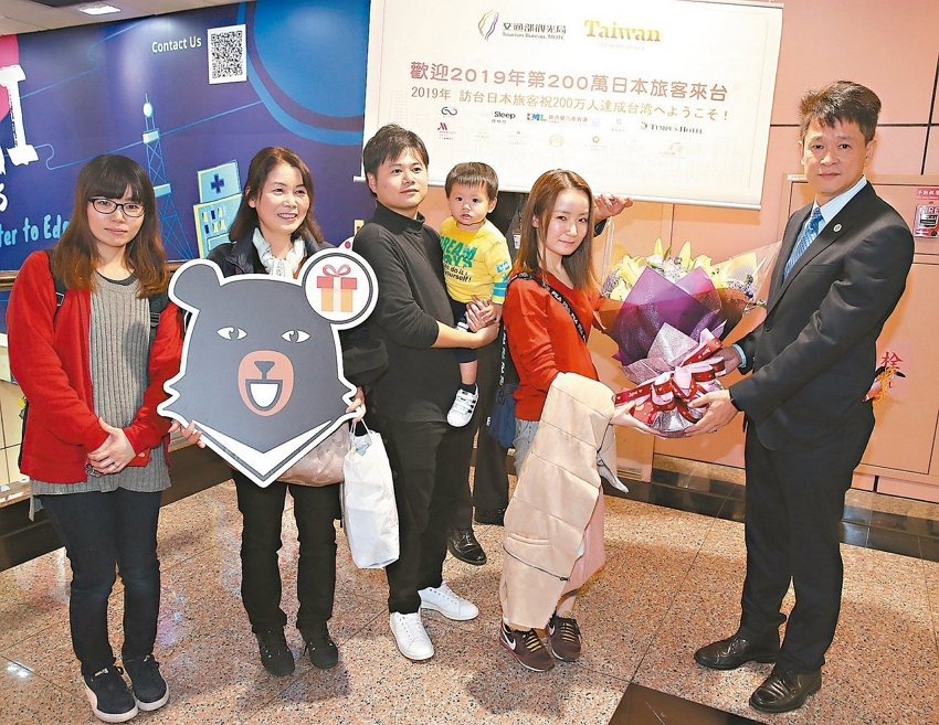 Huang Shih-fang (right), head of the Tourism Bureau's International Affairs Division, welcomes the two millionth Japanese visitor (second right) to Taiwan Dec. 9 last year at Taoyuan International Airport, highlighting a record-setting year for inbound international tourism. (UDN)