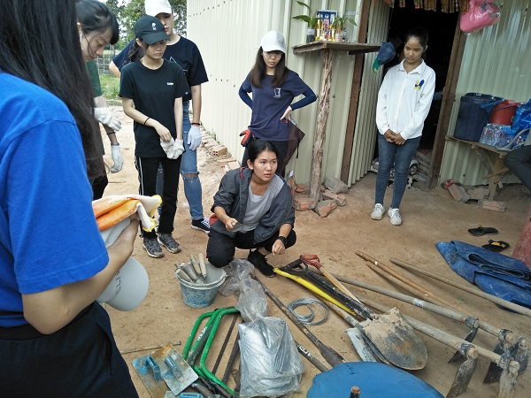 Bun Chou, an ELIV group leader, introduces the tools used to build an outdoor toilet during a volunteer mission to Siem Reap. (Photo by Oscar Chung)
