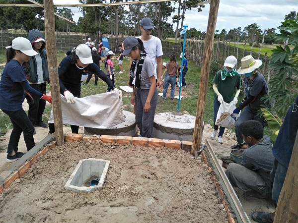 Volunteers construct an outdoor toilet in Siem Reap. (Photo by Oscar Chung)