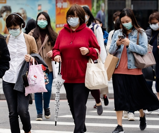 Pedestrians cross the road while wearing surgical masks in Taipei. Taiwan's success managing the COVID-19 pandemic has been attributed in part to the high awareness of disease prevention best practices among the public. (Photo by Chin Hung-hao)