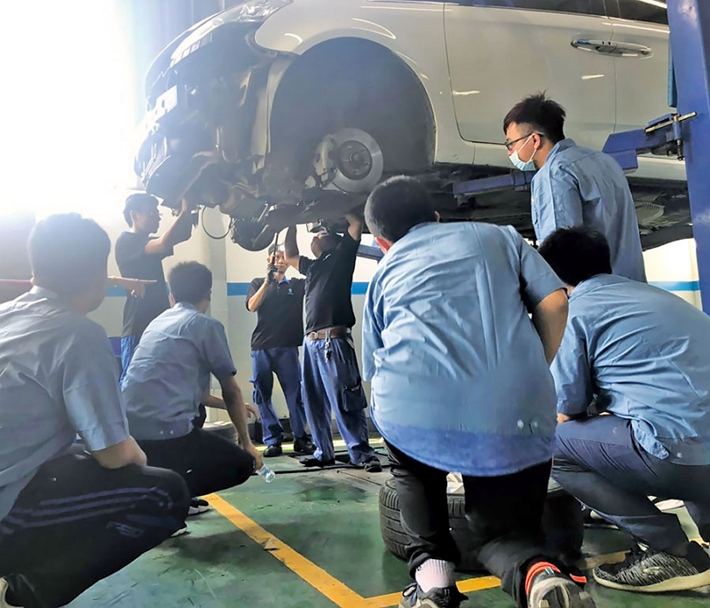 Vocational high school students dressed in light blue shirts watch as staffers work on a car during a trip to Taiwan enterprise Phuc Lap Motors Co. in Vietnam held under the Ministry of Education's Program for New Resident Children's International Workplace Experience. (Photo courtesy of K-12 Education Administration, Ministry of Education)