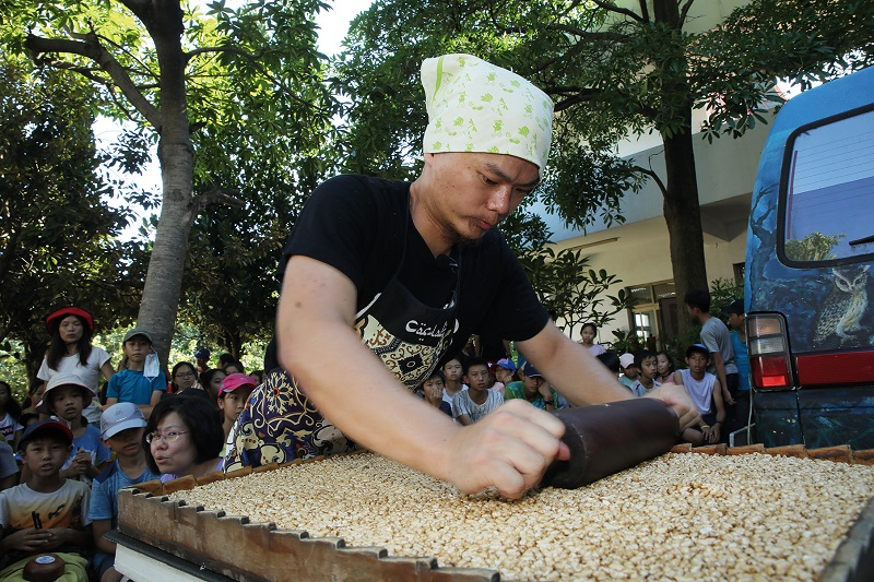 Flattening the mixture with a wooden roller. (photo by Jimmy Lin)