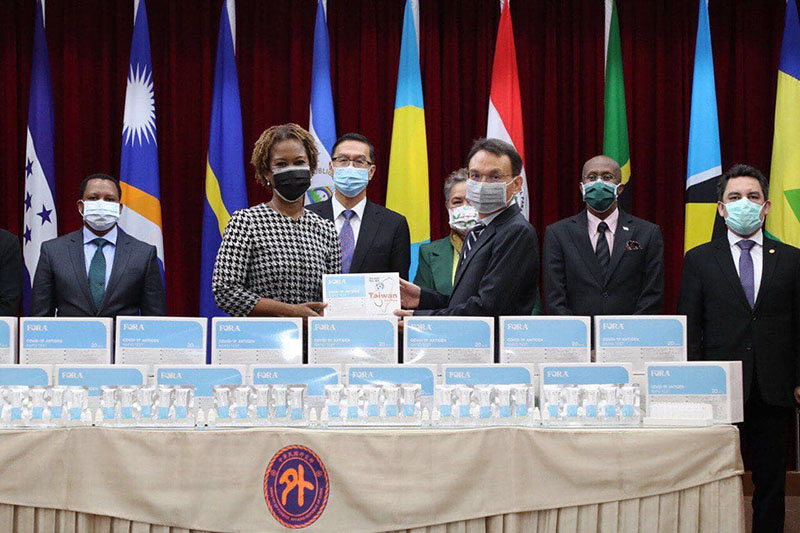 TaiDoc Technology Corp. Chairman Chen Chao-wang (front, right) donates 300K COVID-19 rapid testing kits to St. Kitts and Nevis Amb. Jasmine E. Huggins (front, left) as MOFA Vice Minister Miguel Li-jey Tsao (back, second left) and members of the foreign diplomatic corps in Taiwan look on during a ceremony Dec. 23 in Taipei City. (MOFA)